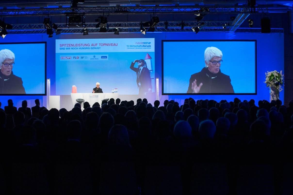 Frau referiert auf Bühne vor Leinwänden am Wirtschaftsforum 2015