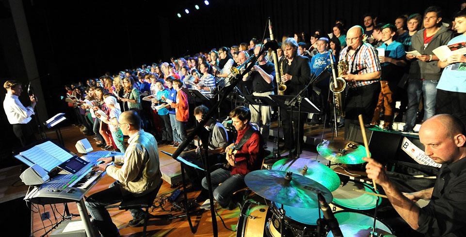 Musiker und Musikerinnen spielen auf der Bühne