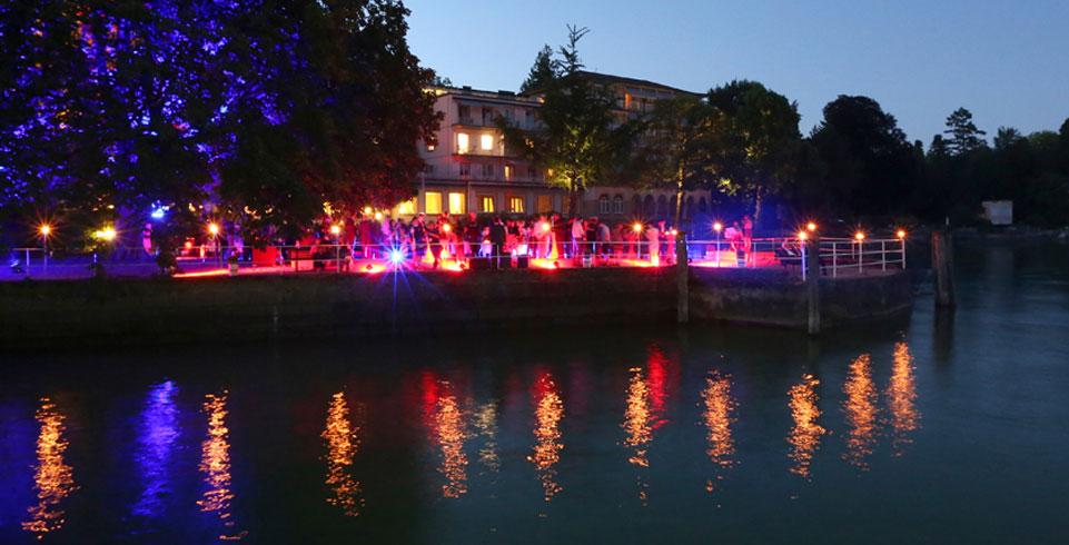 Beleuchtetes Seeufer mit stehenden Menschen an der Lindauer Nobelpreisträgertagung