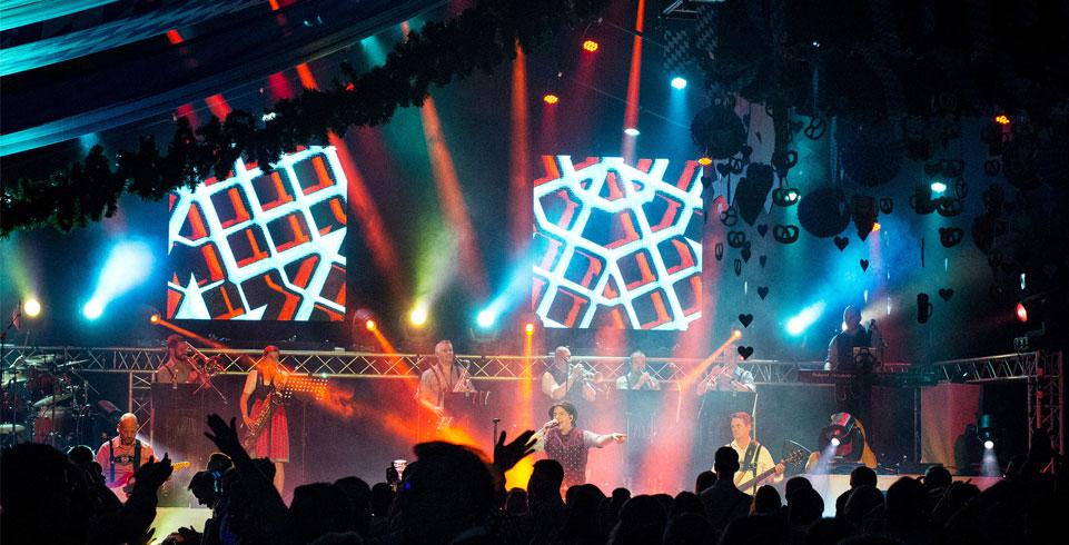 Musiker stehen auf Bühne vor LED-Walls