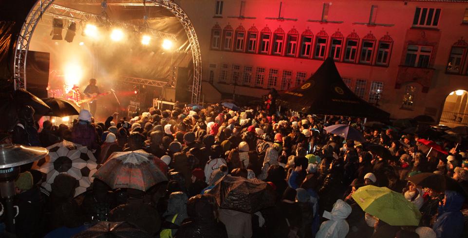 Stehende Menschen blicken zu den Sängern auf der Bühne