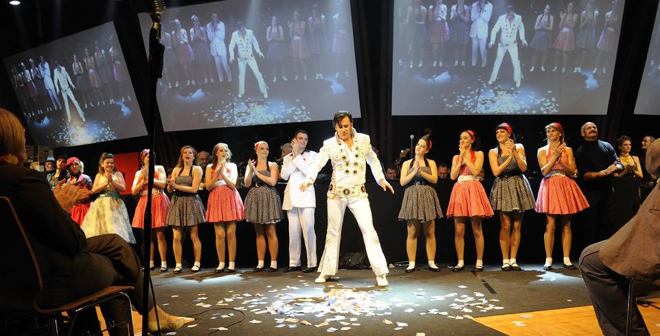 Elvis tanzt mit drei Leinwänden im Hintergrund