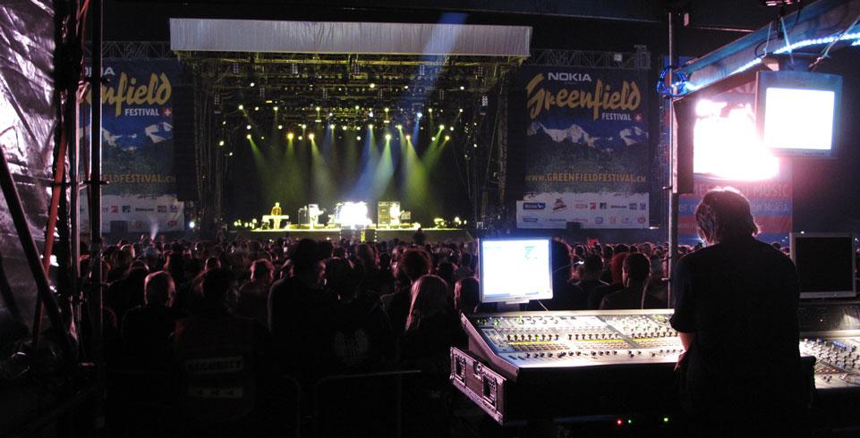 Mann am DJ Pult, im Hintergrund die Bühne und das Publikum am Greenfield Festival