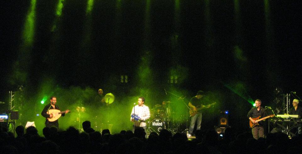 Khaled steht auf beleuchteter Bühne