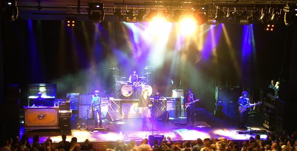 Zuchhero und vier weitere Musiker steht auf beleuchteter Bühne