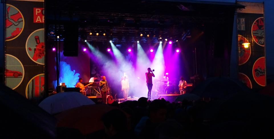 Musiker singt auf beleuchteter Bühne vor Publikum