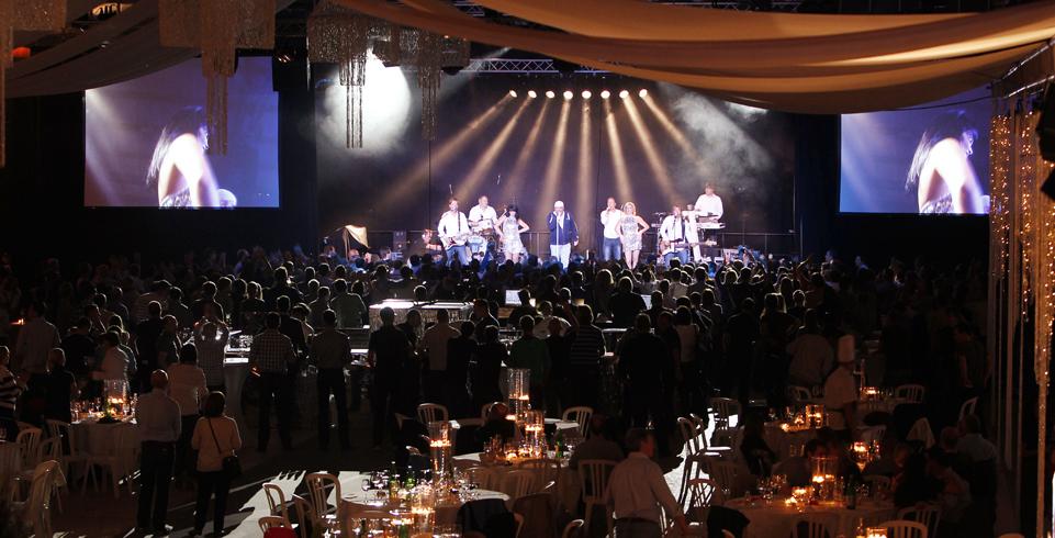 Das Publikum an den Tischen blickt auf die beleuchteten Musiker auf der Bühne