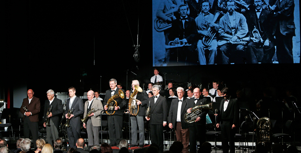 Musiker und Musikerinnen auf der Bühne vor Leinwand beim Jubiläumskonzert der Harmoniemusik Vaduz