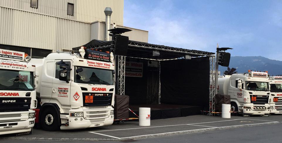 Bühne mit Lautsprechern umgeben von Lastwagen