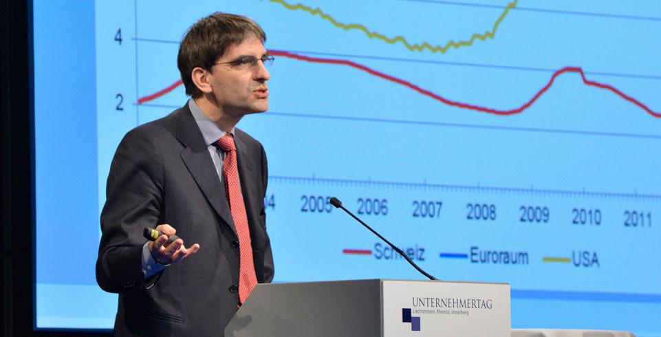 Mann referiert am Rednerpult vor einer Leinwand am Unternehmertag 2014