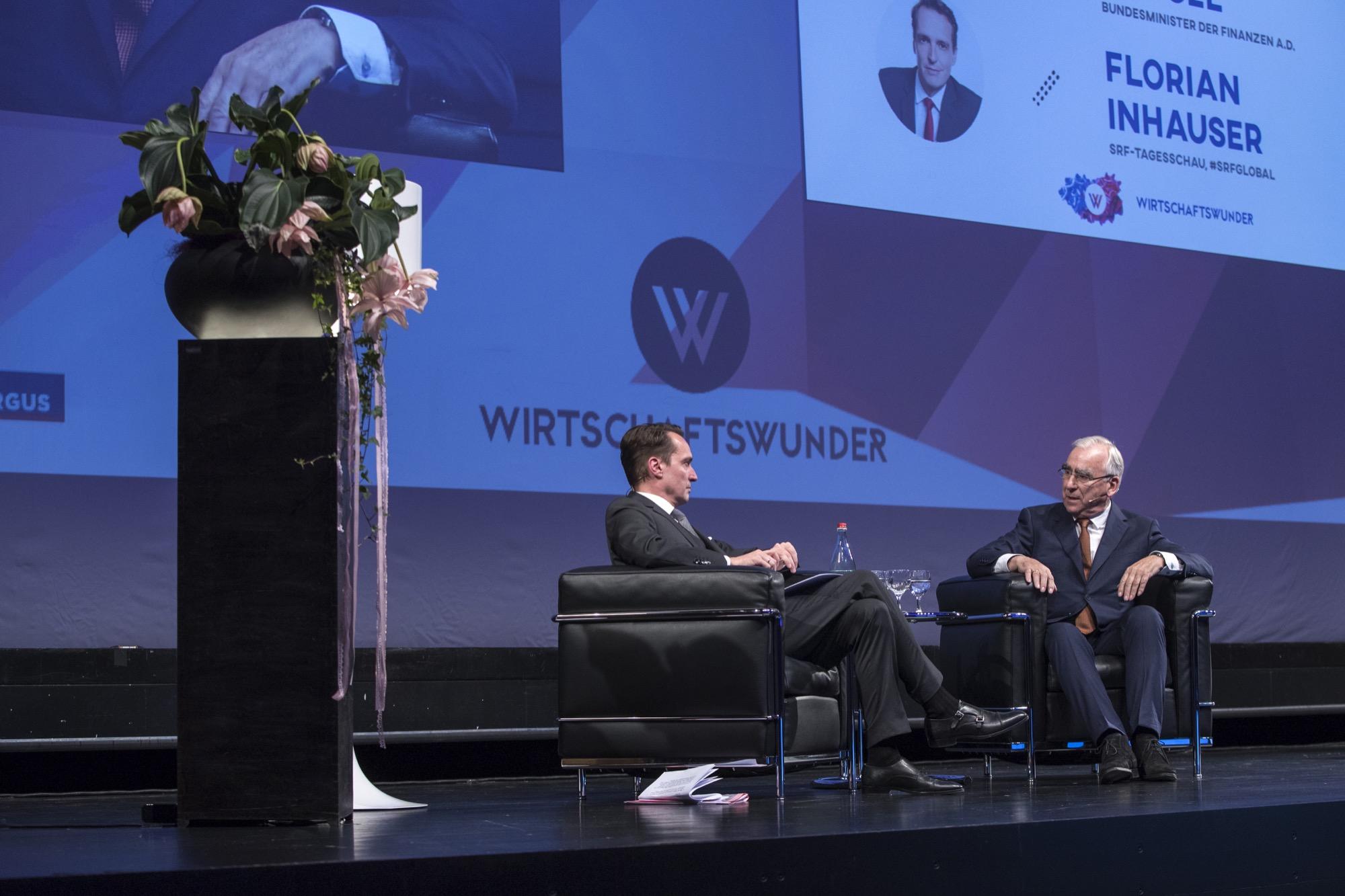Zwei diskutierende sitzende Männer vor einer Leinwand