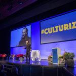 Mann referiert auf Bühne vor Projektion am Finanzforum 2018