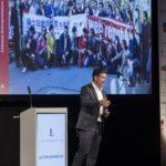 Referent steht am Rednerpult vor Leinwand am Unternehmertag