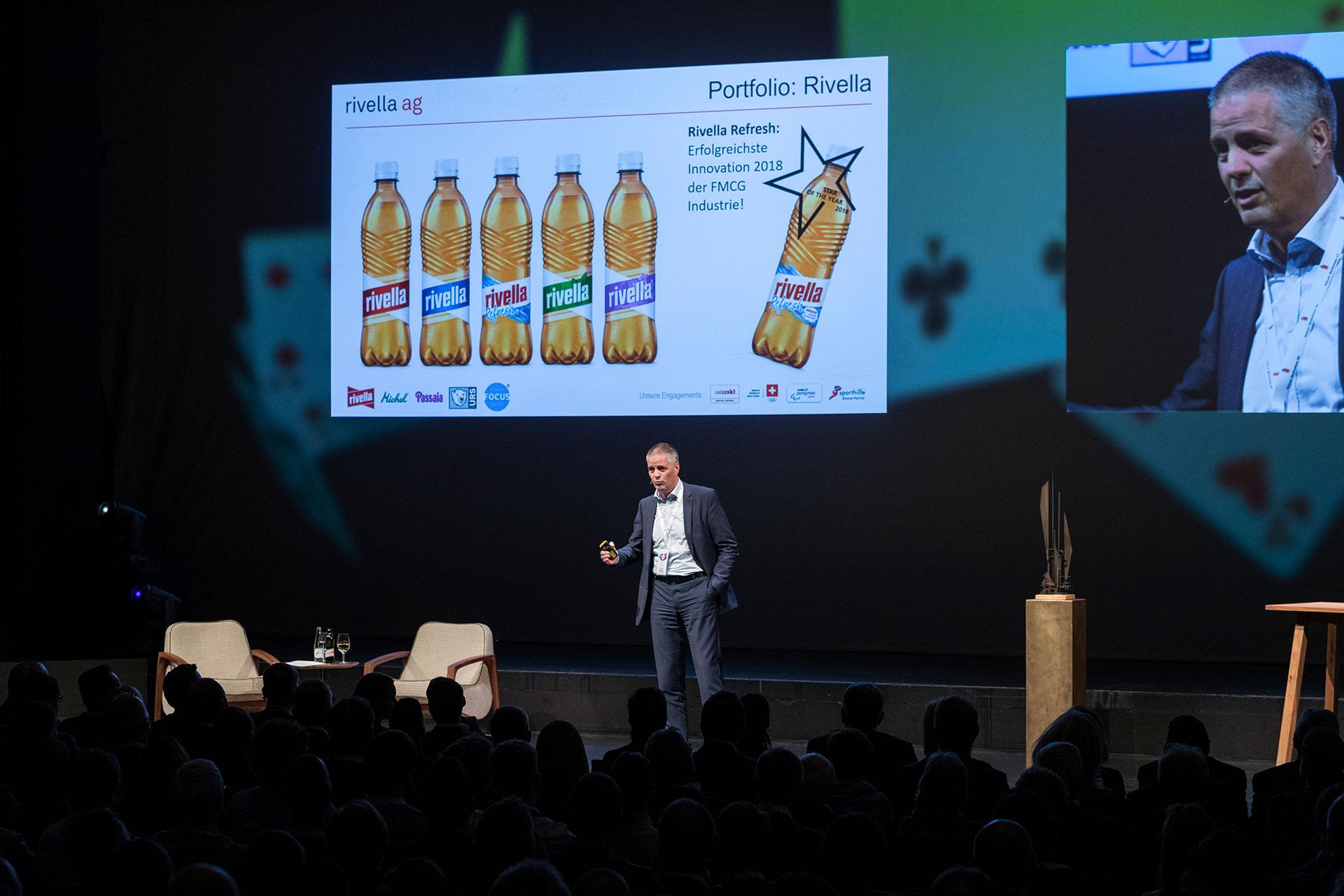 Mann referiert auf Bühne am Finanzforum Liechtenstein 2019 vor Leinwand