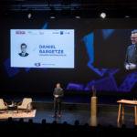 """Daniel Bargetze referiert auf Bühne vor Leinwand und Scheinwerfern beim Wirtschaftswunder 2019 """"Facing Risk"""""""