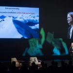 """Edith Schmid referiert vor Leinwand am Wirtschaftswunder 2019 """"Facing Risk"""""""