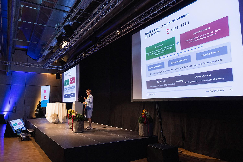 Antoinette Hunziker-Ebneter referiert am Finance Forum vor Leinwand